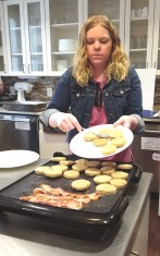 Kristin pushes frozen sausage patties off a plate and onto an electric griddle to sizzle alongside the bacon.